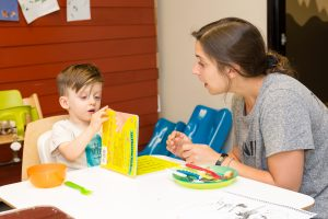 Speech therapist engaging in a speech therapy session with a toddler.