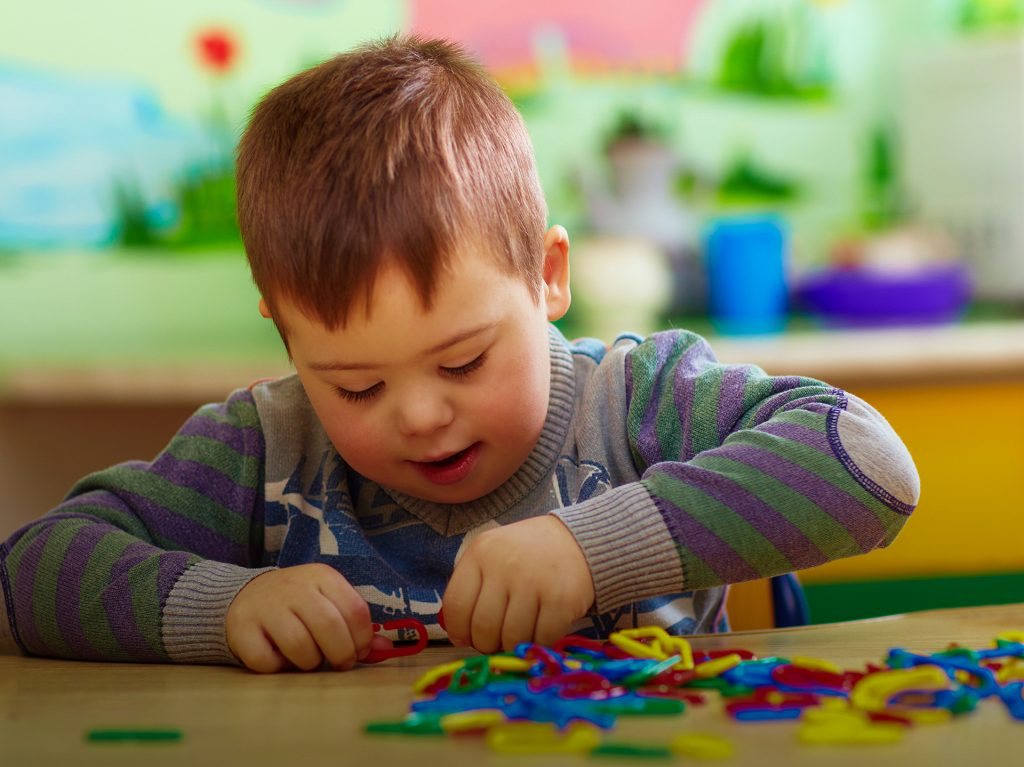 Child with Down Syndrome plays with toys.